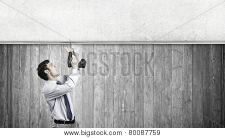 Young businessman using drill to fix banner