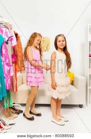 Girl helping another one by fitting the dress