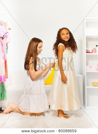 Friend helps another girl to fit beautiful dress