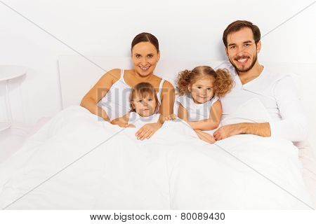 Happy father, mother and two kids lay on white bed