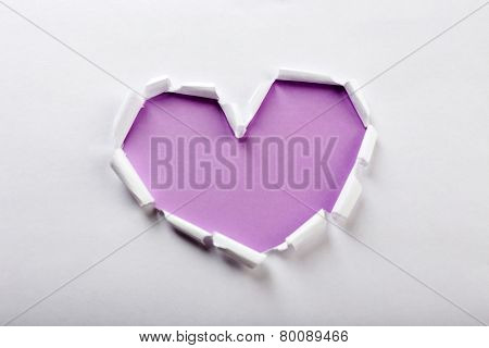 White torn paper heart over purple background