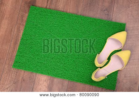 Green carpet on floor and shoes close-up
