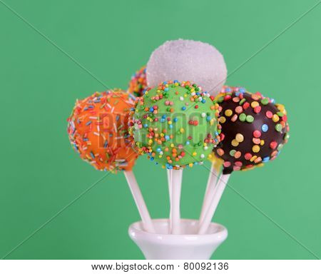Sweet cake pops in vase on green background