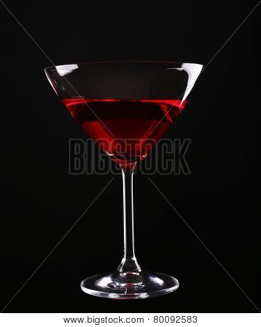Colorful alcoholic beverage in glass on dark background