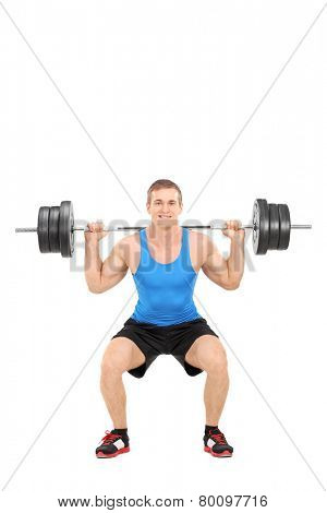 Full length portrait of a strong man exercising with a barbell isolated on white background