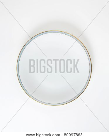 white plate with blue and gold rim on white background