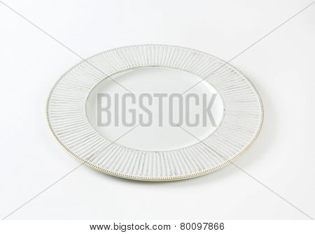 white plate with gold fluted rim on white background