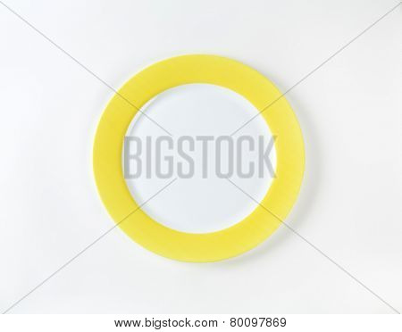 white plate with yellow rim on white background