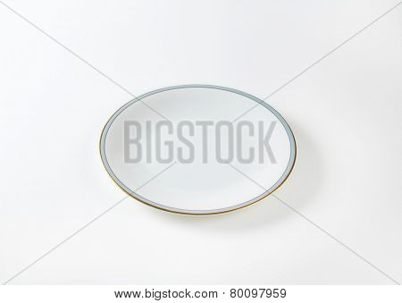 empty white plate with blue and gold rim on white background