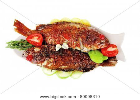 savory : roast golden fish served on fish plate with lemon tomatoes and rosemary