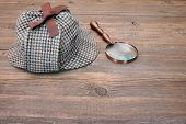 foto of sherlock  - Deerstalker or Sherlock Hat and magnifying glass on Old Wooden table - JPG