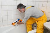 foto of plumber  - Plumber caulking bath tube with silicone glue using cartridge - JPG