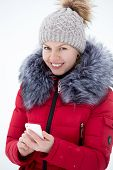 picture of beanie hat  - Happy beautiful girl in knitted hat and red winter coat outdoors against the snow using mobile phone touches the screen of smart phone texting looks in camera - JPG