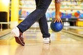 picture of bowling ball  - Male legs and bowling ball in alley background - JPG