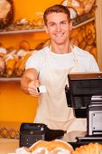 stock photo of cashiers  - Handsome male cashier stretching out plastic card and smiling while standing in bakery shop