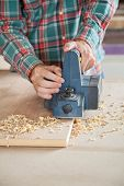 pic of workbench  - Midsection of carpenter using electric planer on plank at workbench - JPG