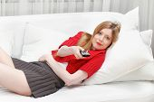 pic of couch potato  - Young girl being lazy at home laying on sofa and holding remote control