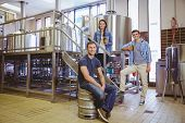 picture of keg  - Man siting on keg and his colleague holding a glass of beer in the factory - JPG
