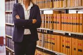 foto of librarian  - Mature female librarian posing with crossed arms in library - JPG