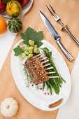 image of crust  - Herb crusted rack of lamb garnished with asparagus green grapes and pomegranates - JPG