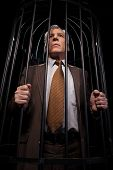 picture of white collar crime  - Low angle view of rustrated senior man in formalwear standing in cell and looking away while isolated on black background - JPG
