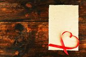 foto of revelation  - Blank sheet of paper with ribbon in heart shape on rustic wooden table background - JPG