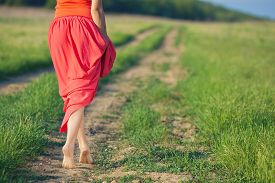 pic of girl walking away  - Bare feet of a young woman walking along a rural country road in the summer - JPG