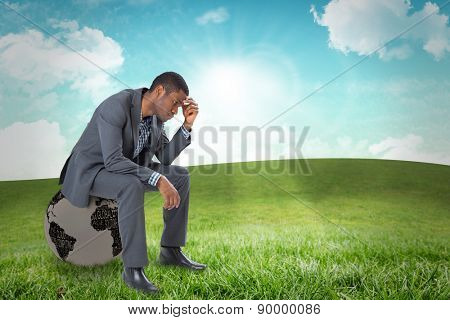 Thinking businessman sitting against field and sky