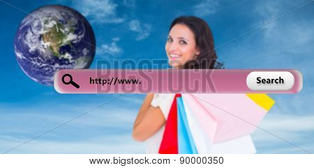 Pretty brunette with shopping bags against blue sky
