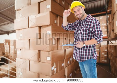 Happy repairman wearing hard hat while holding clipboard against shelves with boxes in warehouse