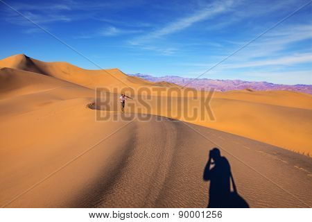 Orange sand dunes in Death Valley, California. A middle-aged woman in striped T-shirt carries a camera and tripod