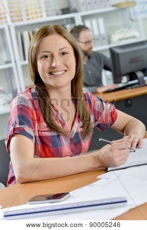 Smiling lady sat at desk