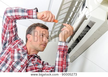 Man working on air conditioning unit, flap open