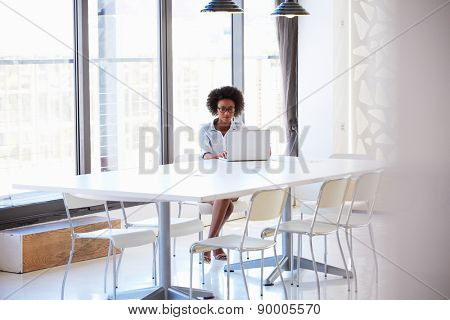 Young woman working in empty meeting room