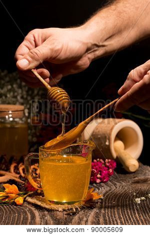 Honey dripping from a wooden honey dipper in a jar from man hand