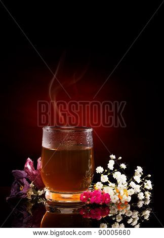Cup of hot tea. Tea Steam. Flowers near. Red Spotlight on black background