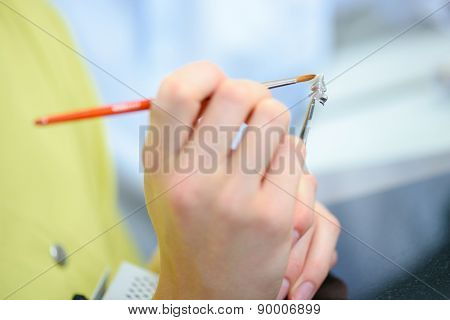 Dentist preparing a false tooth