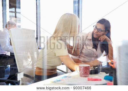 Women coworkers talking in an office