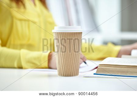 people and education concept - close up of female hands with books and coffee cup