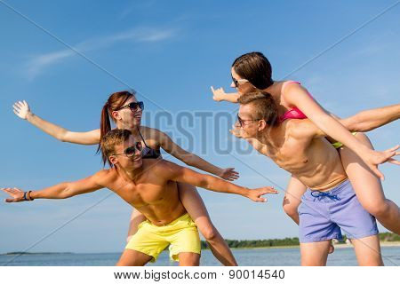 friendship, sea, summer vacation, holidays and people concept - group of smiling friends wearing swimwear and sunglasses having fun on beach