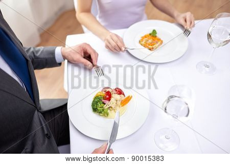 restaurant, food, people, date and holiday concept - close up of couple eating appetizers at restaurant