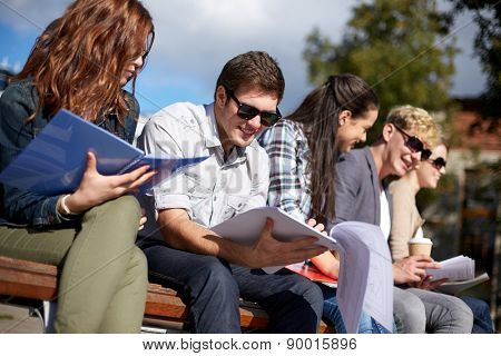 summer, friendship, education and teenage concept - group of happy students with notebooks learning at campus