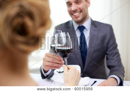 restaurant, people, celebration and holiday concept - close up of young couple with glasses of red wine looking at each other at restaurant