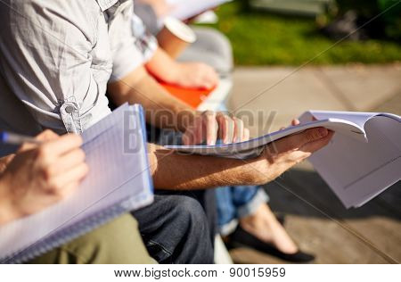 summer, friendship, education and teenage concept - close up of students with notebooks reading and writing at campus