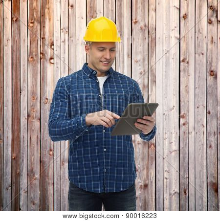 repair, construction, building, people and maintenance concept - smiling male builder or manual worker in helmet with tablet pc computer over wooden fence background