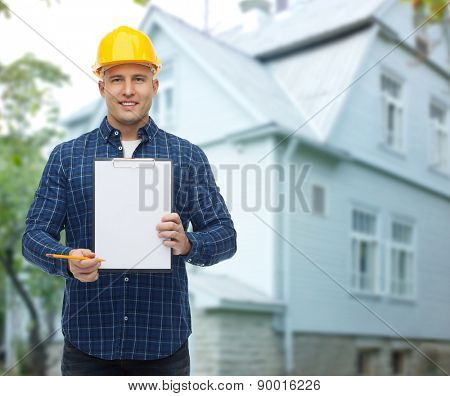 repair, construction, building, people and maintenance concept - smiling male builder or manual worker in helmet showing blank paper on clipboard over living house background