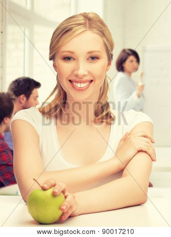 picture of beautiful girl with green apple at school