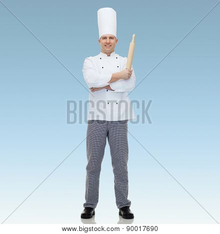 cooking, profession and people concept - happy male chef cook holding rolling pin  over blue background
