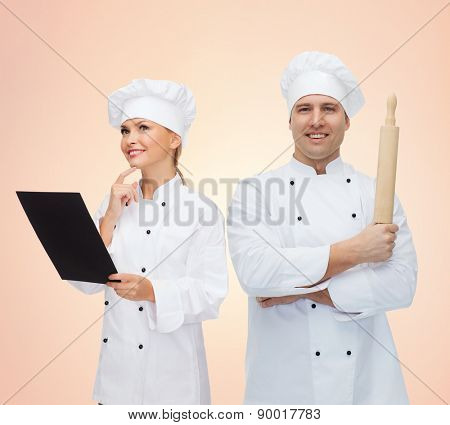 cooking, baking, teamwork, profession and people concept - happy chefs or cooks couple with menu and rolling pin over beige background