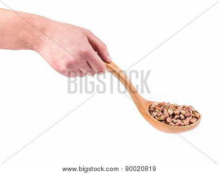 Wooden spoon with pistachios in hand.